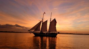 ship schooner sailing at sunset with red and gold colors